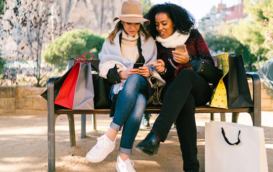 Woman on an outdoor bench surrounded by shopping bags