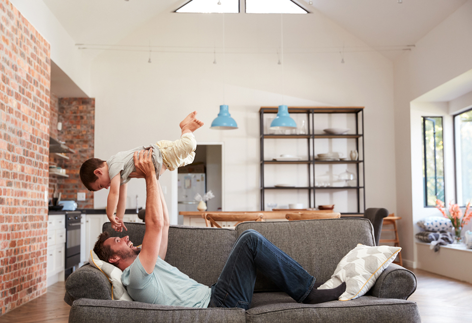 Father holding up baby in new house after buying a new home