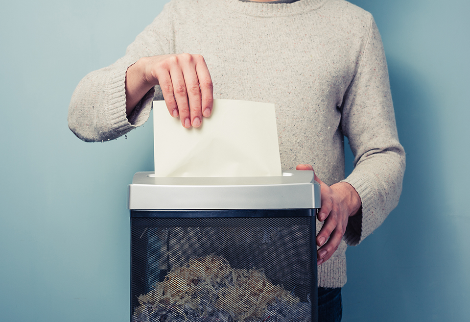 Person shredding their secure paperwork, keeping their financial data safe